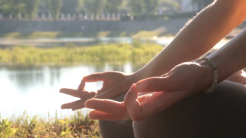Young woman sits in lotus pose with hands jnana mudra in park outdoors. Female in padmasawa pose, arms are kneeling, thumb and forefinger are connected, forming circle. Serene lady dressed in gray #34433239