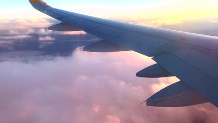 Airplane flight. Wing of an airplane flying above the clouds with sunset sky. View from the window of the plane. Aircraft. Traveling by air. 4K UHD video