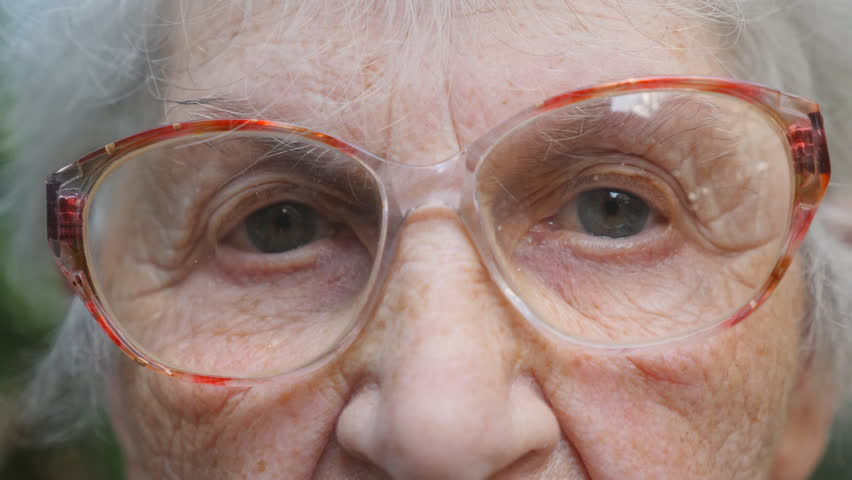 Old woman in eyeglasses looking into camera. Slow motion