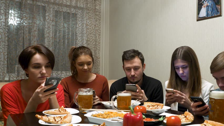 Group of friends at dinner party with all people on the table occupied with cellphones. #34460302