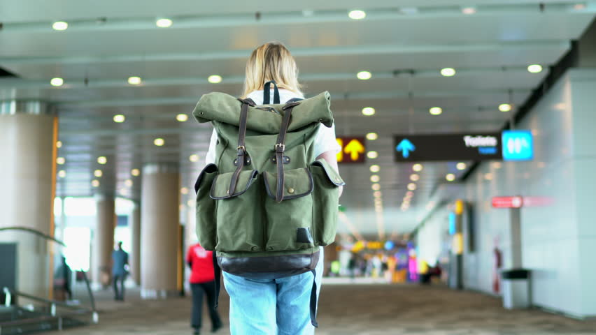 Rear view of female tourist carrying rucksack with copy space area for brand name or logo walking to gate in airport terminal  | Shutterstock HD Video #34471645