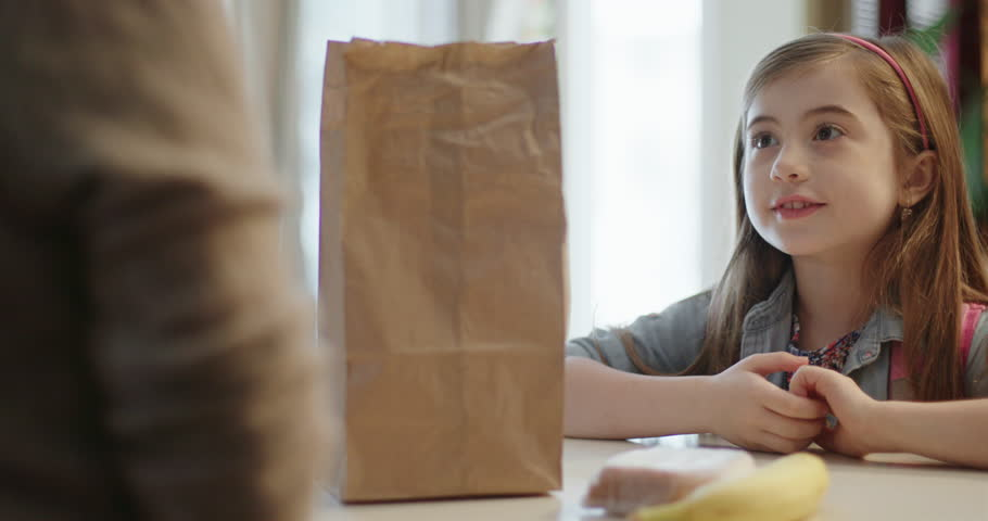 Mother Packs Lunch for Daughter. a countertop view of a mother placing a sandwich in a bag and handing the lunch bag to her daughter. She says Thank You and exits #34473805