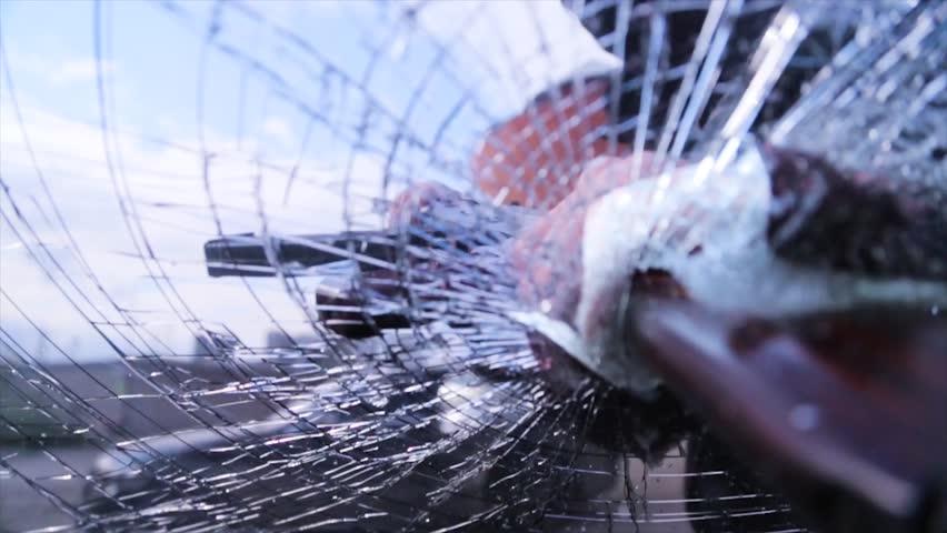 Bandit in a black mask breaks the glass of the machine. Thug smashes the windshield machine gun Kalashnikov