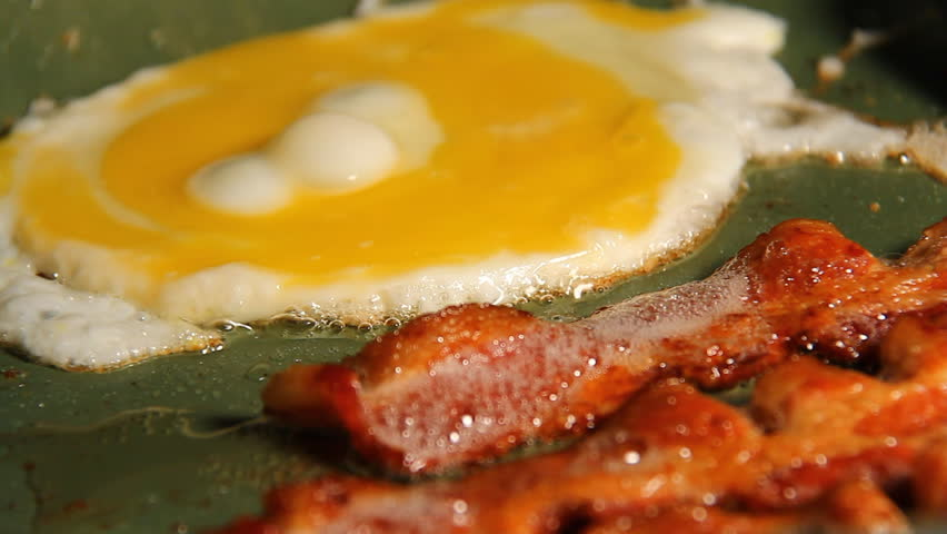 Bacon and Eggs. Three strips of bacon frying in a pan with an egg getting flipped. #3447974