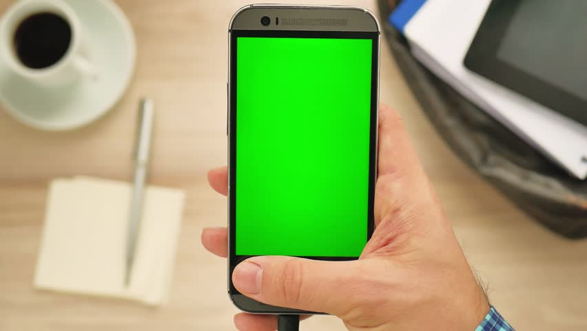 Man using a modern smartphone with green screen at her desk - green screen for placement of your own content | Shutterstock HD Video #34498990