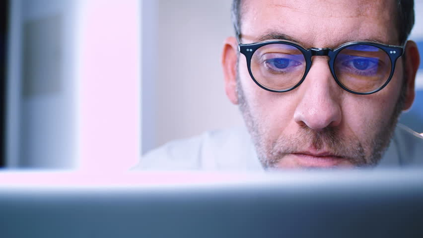 Close up dolly shot of a mature man looking intently at computer display with the reflection of windows & charts in his glasses | Shutterstock HD Video #3450098
