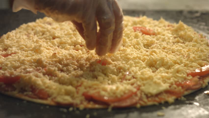 Cooking of pizza. 3 Shots. Slow motion. 1. Female hands sprinkle cheese pizza. Close-up. 2. Female hands spread cheese on pizza. Top view. 3. The pan with pizza is placed in the oven.  | Shutterstock HD Video #34502995