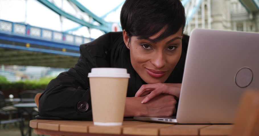 Gorgeous black woman resting her head on a table looks at the camera casually in London, England. Beautiful young female with her laptop stares at the camera at a cafe near the Tower Bridge. 4k | Shutterstock HD Video #34513126