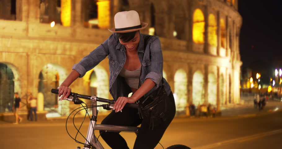 Pretty young African woman traveling in Rome, Italy out sightseeing on her bicycle at night. Smiling ethnic millennial female poses for the camera on her bike near the Colosseum in Rome. 4k | Shutterstock HD Video #34513717