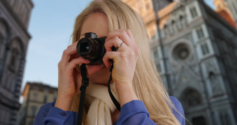 Happy young tourist exploring Florence, Italy takes photos on her digital camera to show people back home. Caucasian blonde female capturing memories on her camera near the Florence Cathedral. 4k