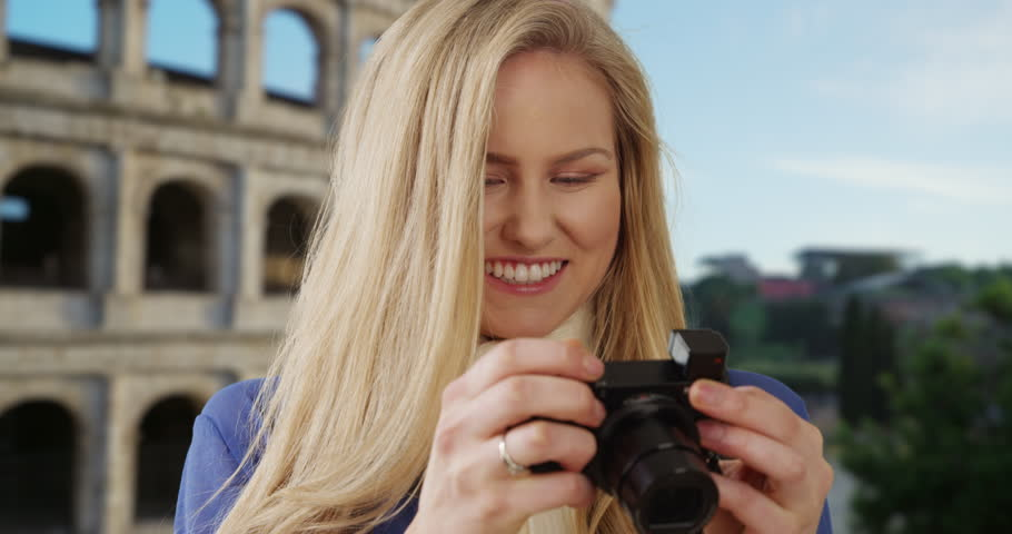 Young female tourist traveling in Rome takes photos near the Colosseum. Adventurous Caucasian woman in Rome, Italy takes pictures to show her friends back home. 4k