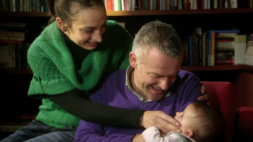 Portrait of happy married people and child bearing, wife and husband playing and smiling with little daughter at home