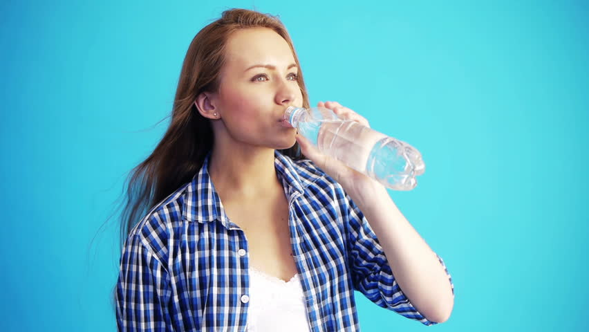 pretty woman drinking water from bottle