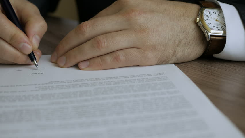 Businessman signing business contract agreement, close up of male hand with pen writing signature. The man corrects and fills the document.