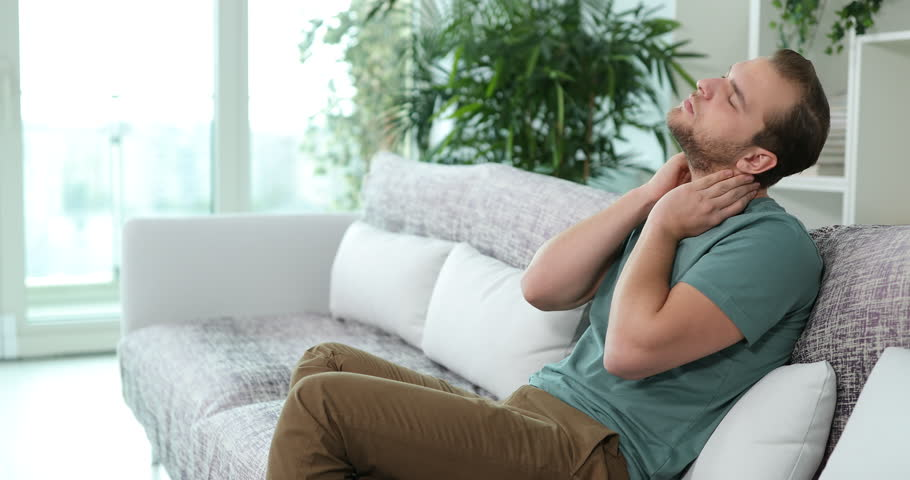 Sad Man Suffer Alone from Neck Pain Cramp Problem Sitting on Sofa in Living Room | Shutterstock HD Video #34570222