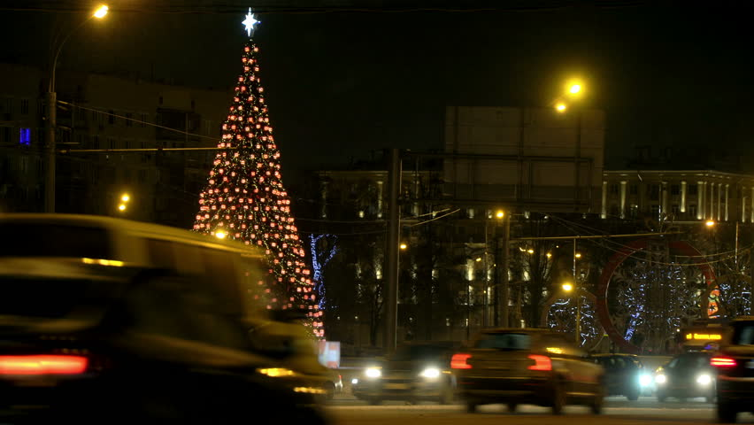 Christmas tree glows brightly in night city winter snow-covered road amid traffic jam passing cars, concept Christmas eve, new year, snow, blowing Blizzard, cars covered snow, snowflakes in headlights