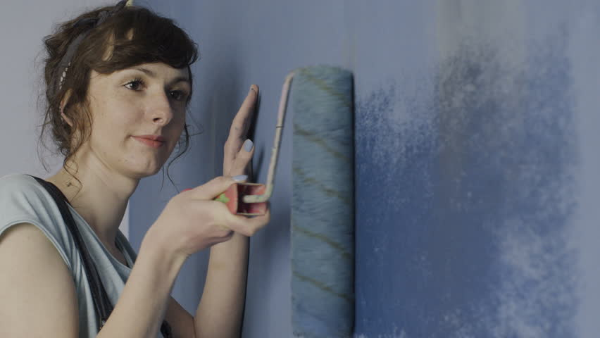 Painting walls with roller.  A young woman painting walls in a blue bedroom in her home with a roller. Close up.  #34594378