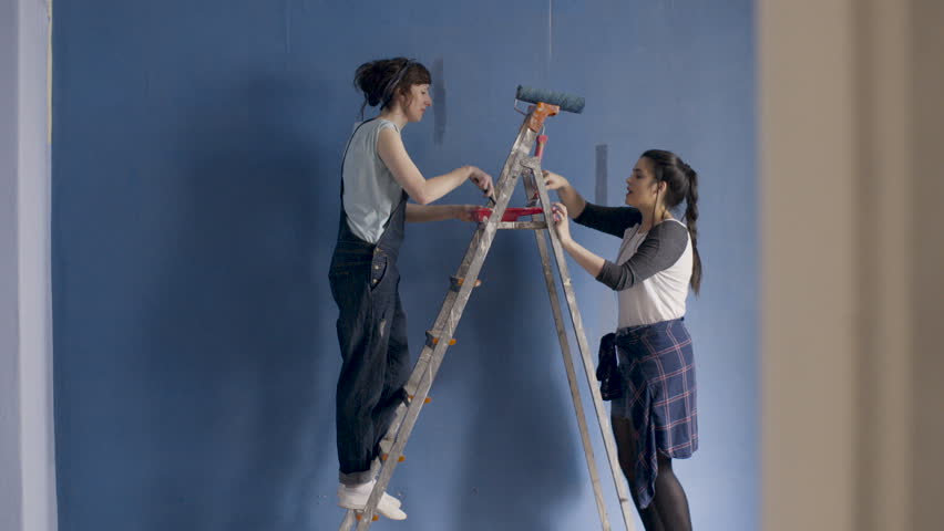 Two funny girlfriends dance sing and paint a walls at home in blue with the help of paintbrushes.    #34594399