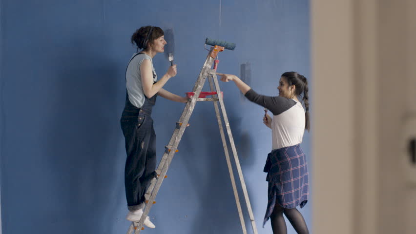 Two happy smiling girls  have fun dancing, singing and painting the blue wall in living room.   #34594402
