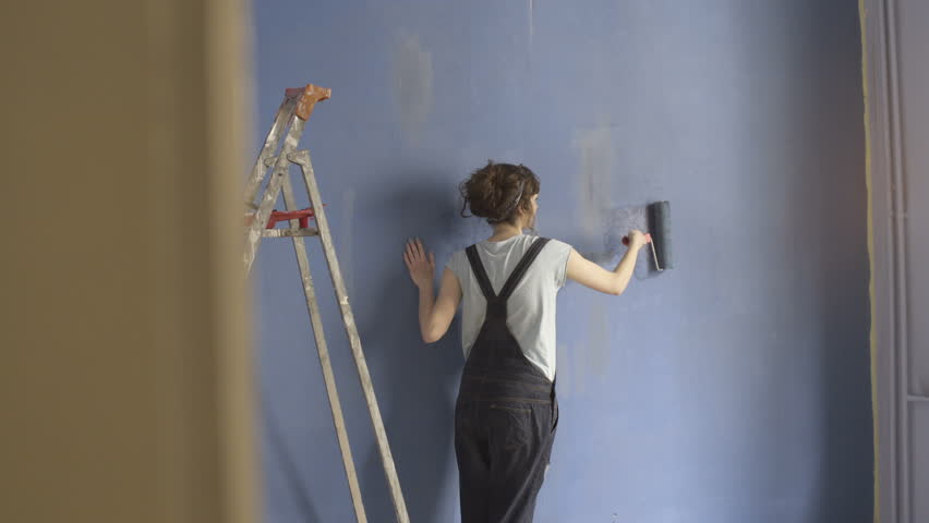 Girl painting blue wall  with roller #34594405