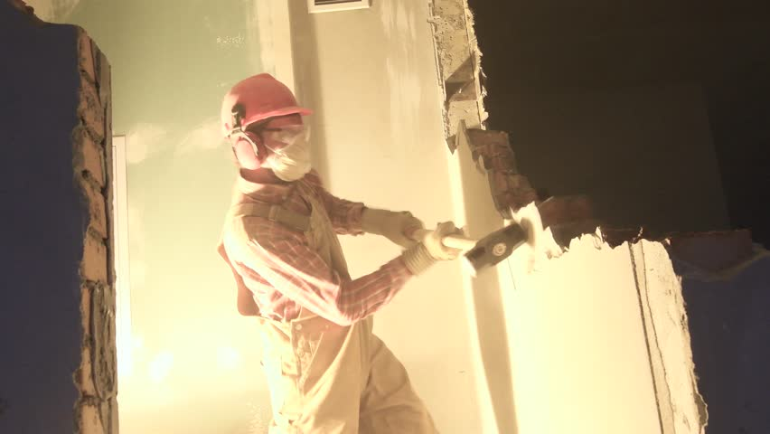 Worker with sledgehammer at indoor wall destroying | Shutterstock HD Video #34603396
