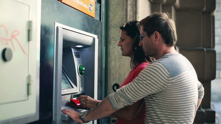 Young couple withdrawing money from an ATM, steadycam shot  Royalty-Free Stock Footage #3461411