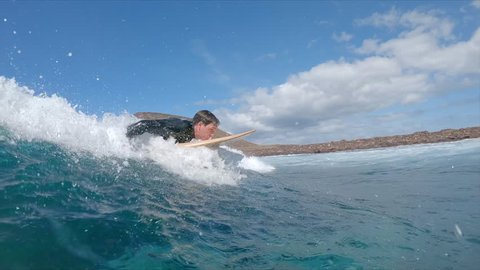 SLOW MOTION, UNDERWATER: Young surfer paddling on his surfboard and catching a cool big wave. Extreme surfboarder surfing glassy clear ocean waves on a sunny day near the volcanic island of Lobos.