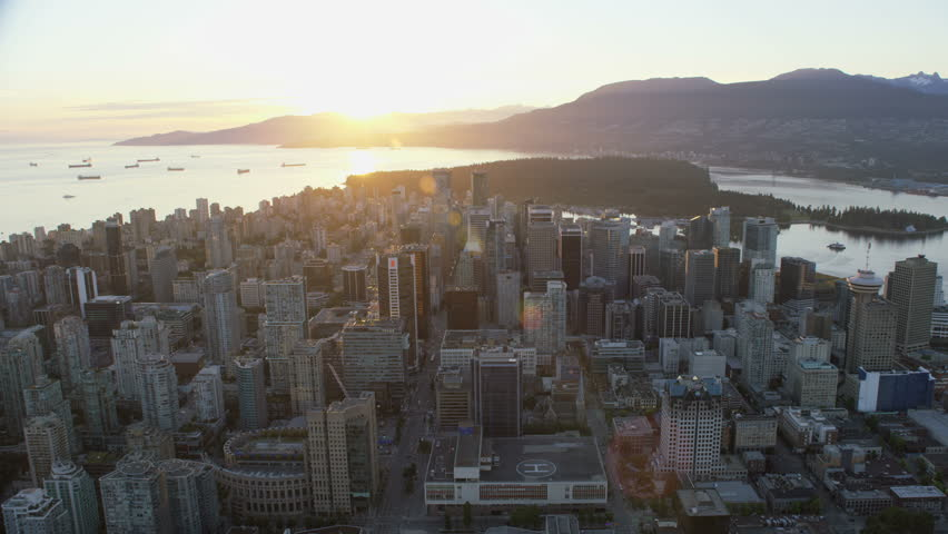 Vancouver Canada - Sept 2017: Aerial overhead view sunset over Vancouver city skyline skyscrapers and helipad Stanley Park Cypress Mountain ranges British Columbia Canada RED WEAPON