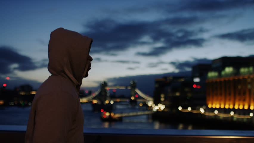 Profile steadicam shot of a hooded male athlete jogging in the city early morning, in slow motion | Shutterstock HD Video #34657597