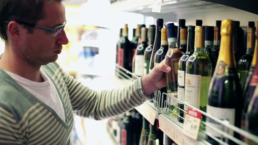 Young Man Choosing Wine In The Shop Steadycam Shot
