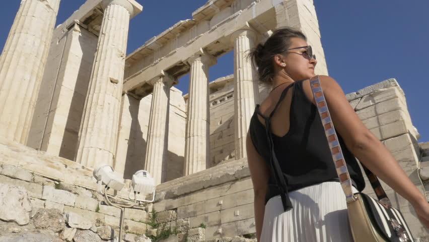 Beautiful young tourist woman walking among Parthenon ruins in Athens Greece
