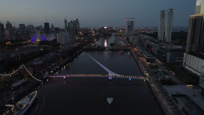 Puerto Madero-Puente de la Mujer Footbridge Woman-Madero Harbor-Buenos Aires at Sunset-City Buildings Night Lights-Argentina-Ciudad de Buenos Aires at Sunset - Argentina - 4k Aerial Drone Scene