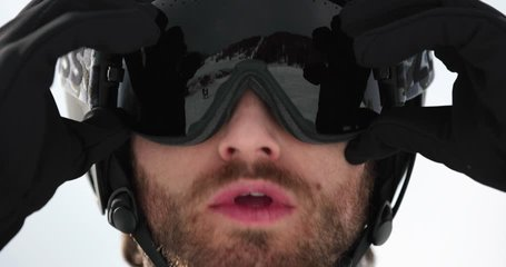 Man face detail adjusting helmet preparing for skiing.Mountaineering ski activity. Skier people winter sport in alpine mountain outdoor.Front view.Slow motion 60p 4k video