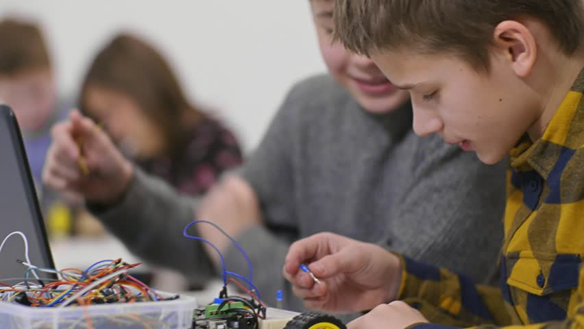 Two boy teenager constructing model bot car with backlighting in practical lesson in technical classroom during extracurricular activities in modern laboratory | Shutterstock HD Video #34716610