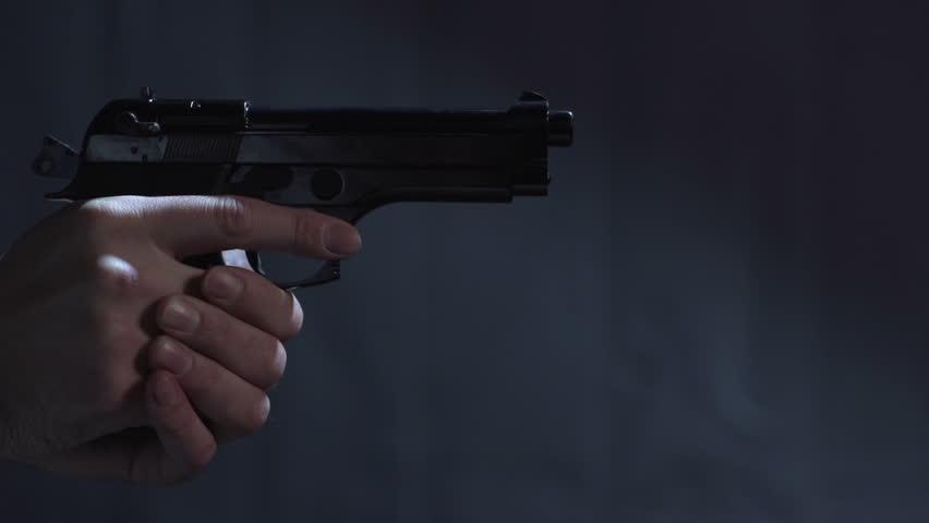 Close profile of man holding a 9 mm handgun takes three shots | Shutterstock HD Video #3473081