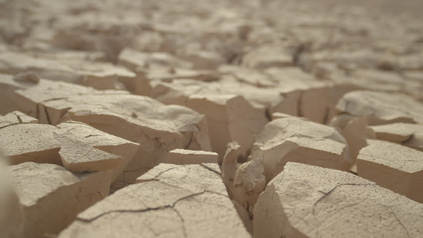MACRO, DEPTH OF FIELD: Dry mud cracks shining in heat create an interesting landscape. Rugged rocky terrain providing no refuge for plants or animals. Global warming drying out once fertile land.