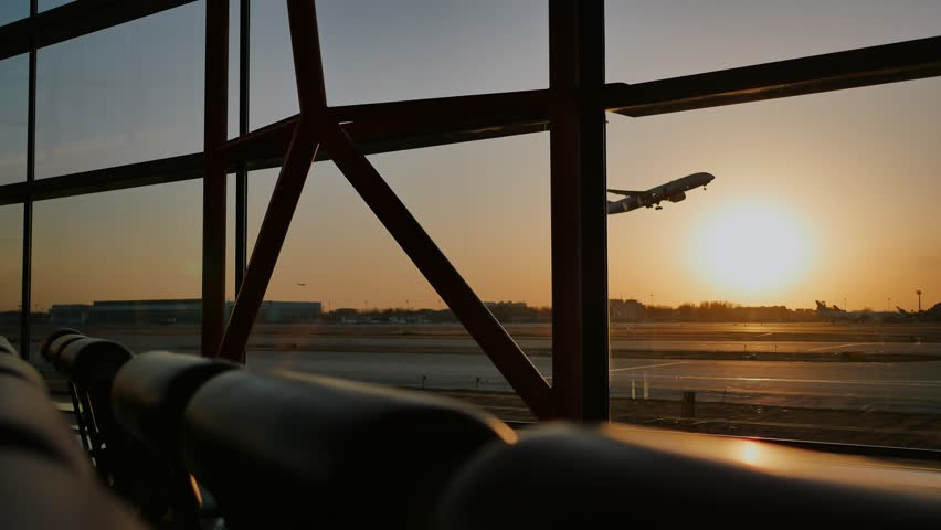 Silhouette of an airplane taking off at sunset at airport in the background of a window.