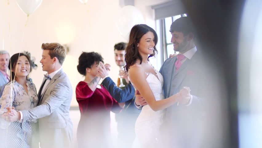 Newly wed couple are dancing together at their wedding with all of their guests.