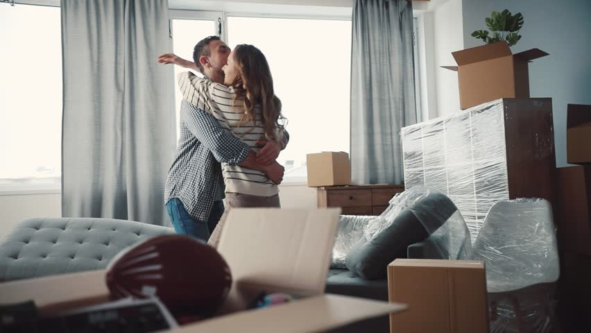 Nice Caucasian couple in love hugging and turning. Young people moving to new apartment. There are unpacked things, new sofa in living room. | Shutterstock HD Video #34760770