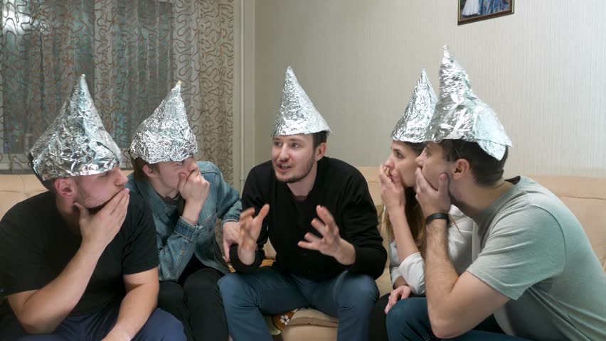 Cinemagraph - Group of people with foil on their heads discussing conspiracy theories. Friends with foil on their heads. You know, so they can't read your mind. Foil on head conspiracy theories