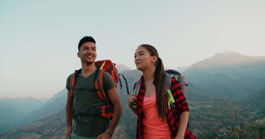 Young asian couple of tourists doing selfie reaching the top of the mountain