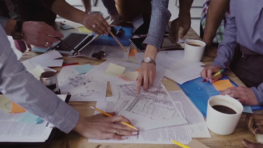 Close-up view of young business team working together near the table, brainstorming. | Shutterstock HD Video #34786561