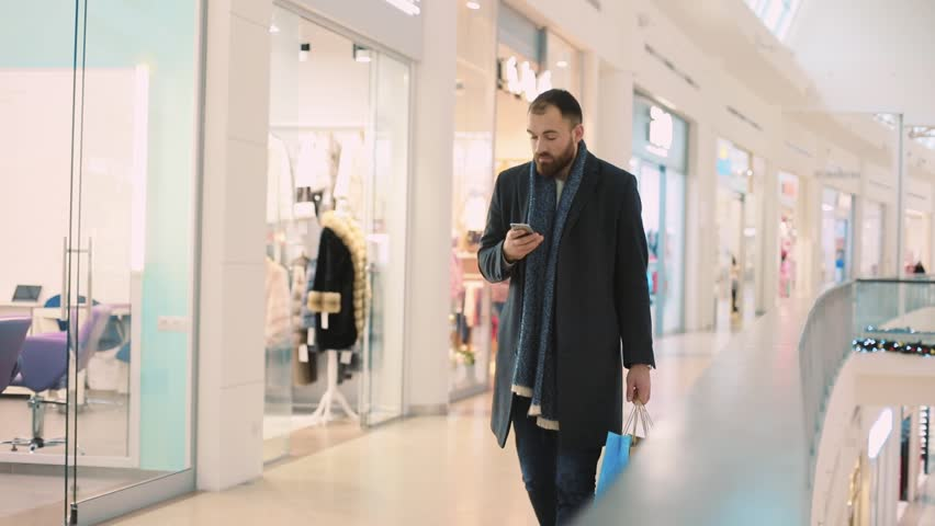 young attractive man with bags use phone walking stopped smile in mall feel happy portrait handsome waiting shopping look around buy close up new year holiday mobile smartphone internet slow motion #34793224