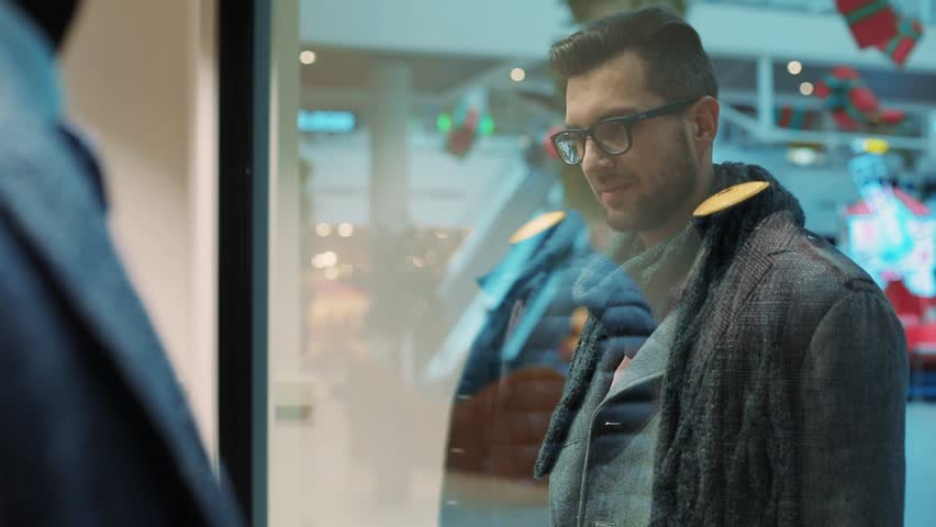 Young attractive man looking at shop window with men's suits in the mall christmas lifestyle building standing design money christmas tree shop store shopaholic storefront slow motion