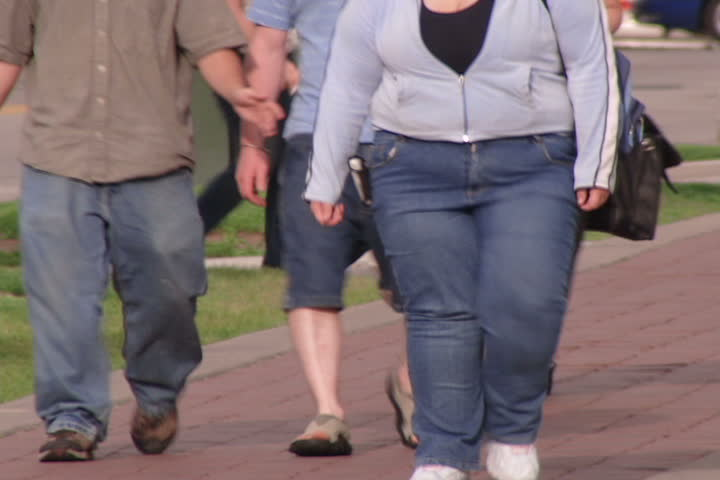 Obese people walking down urban street.