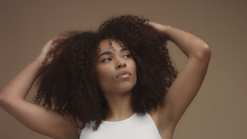 Closeup portrait of mixed race black woman shaked head and her curly hair flying in air slowly. Touching it