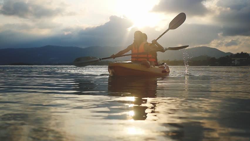 Happy smiling couple kayaking along the sea at beautiful summer sunset. Tourists paddling kayak, teamwork, togetherness. Slow motion. 1920x1080