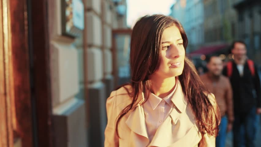 An attractive, beautiful woman in a stylish wear walks through the crowd, observing the architecture of old town. Cheerful mood, having fun. Female portrait, slow motion