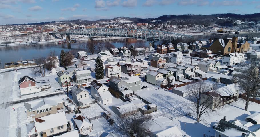 A slow forward winter aerial establishing shot of snow covered roads and houses in a rust belt residential neighborhood. Rochester and Ohio River in the distance. Pittsburgh suburbs.