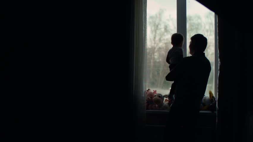 Happy asian family scene, silhouette of father holding baby in hands at window